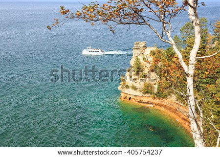 MUNISING MICHIGAN-OCTOBER 10, 2015: A ferry boat carrying tourists passes Miners Castle at Pictured Rocks National Lakeshore in the Upper Peninsula of Michigan on Lake Superior - stock photo