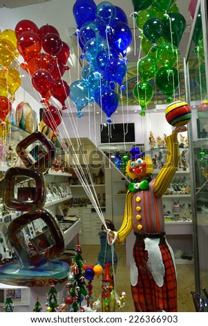 MURANO, ITALY - SEP 25, 2014: Clown with balloons and glass figurines from murano glasses displayed in a shop window.  Murano is home to a vast number of factories  making all manner of glass objects  - stock photo