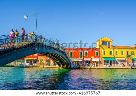 MURANO, ITALY, SEPTEMBER 20, 2015: people are crossing bridge over the main channel on murano island in italy - stock photo