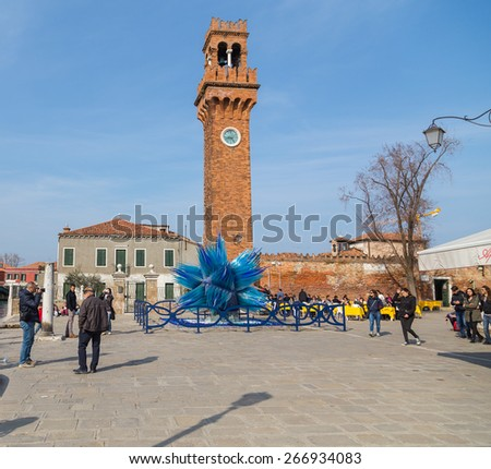MURANO, ITALY - 14TH MARCH 2015: A view of the Bell and Clock Tower in Campo Santo Stefano in Murano. People can be seen in the square. - stock photo