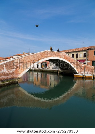 MURANO, ITALY - 14TH MARCH 2015: An old Bridge in Murano, Italy. People can be seen on the bridge and by buildings. - stock photo