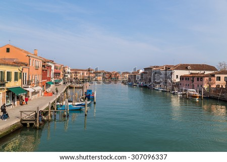 MURANO, ITALY - 14TH MARCH 2015: Buildings and ports in Murano. People can be seen at the waters edge - stock photo