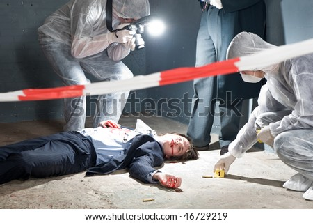 Murder scene with two forensic analysts and a lieutenant investigating a crime on a businessman in a basement - stock photo