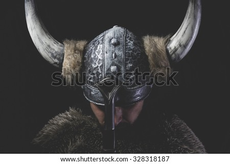 Murderer, Viking warrior with iron sword and helmet with horns - stock photo