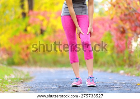 Muscle injury of female sports runner thigh. Woman running muscle strain injury in thigh. Closeup of runner touching leg in muscle pain outside in fall forest. - stock photo