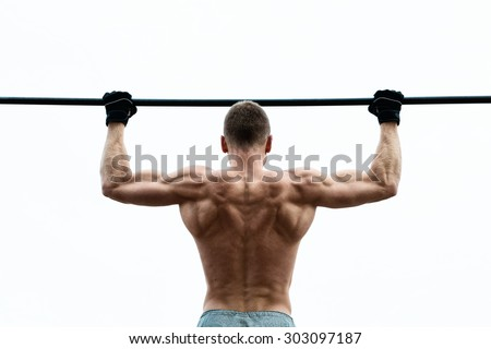 Muscle man making pull-up on horizontal bar against the sky - stock photo