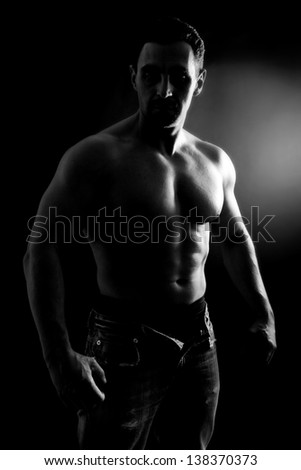 muscle man posing in studio, black and white,black background - stock photo