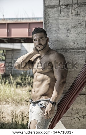 Muscle man shirtless outdoors in building site. Construction worker - stock photo
