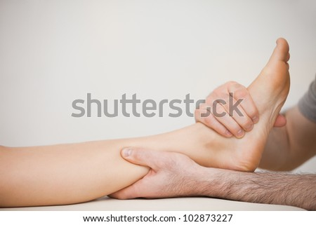 Muscle of a foot being massaged in a room - stock photo