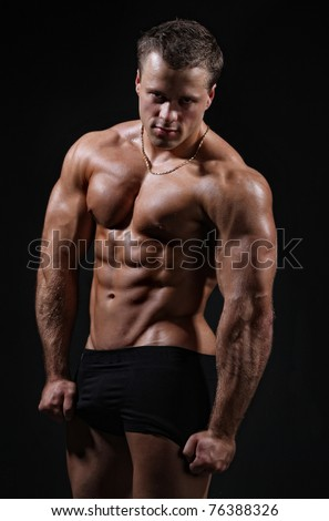 Muscle sexy wet nude young man posing in trunks - stock photo