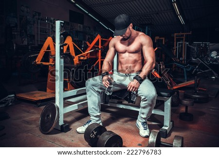 muscle shaped man tired sitting relaxed with weights and energy drink  - stock photo