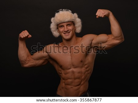Muscled male posing in winter hat - stock photo