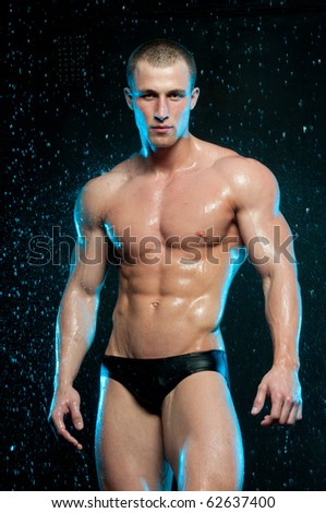 Muscled man posing in studio with water drops - stock photo