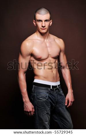 Muscled model posing in studio - stock photo