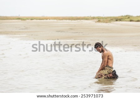 Muscled Shirtless Soldier in Camouflage Pants and Black Shoes Kneeling at the sea water  - stock photo