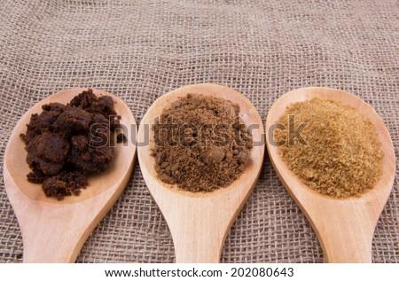 Muscovado sugar, brown sugar and coconut sugar n wooden spoon on gunny sack - stock photo