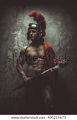 Muscualr man in a Roman clothes with sword. - stock photo