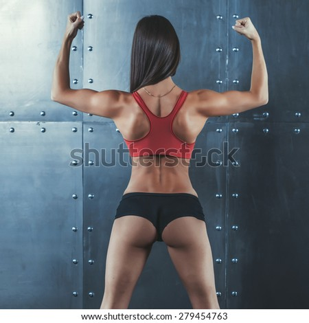 Muscular active athletic young woman with sexy buttocks showing muscles of the back shoulders and hands fitness, sport, training and lifestyle concept - stock photo