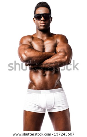 Muscular african guy with crossed arms facing camera, studio shot. - stock photo