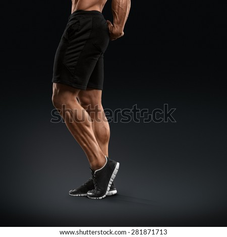 Muscular and fit bodybuilder fitness male model posing over black background. Strong and handsome young man demonstrate his muscular legs. Body of muscular male with great physique - stock photo