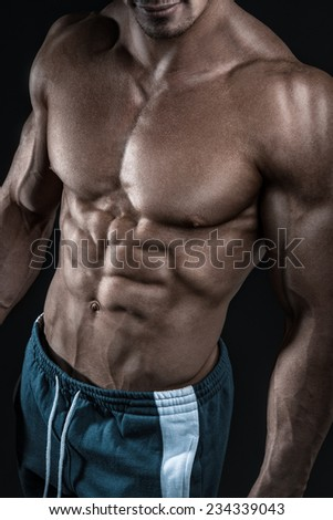 Muscular and fit young bodybuilder fitness male model posing over black background. Studio shot on black background. - stock photo