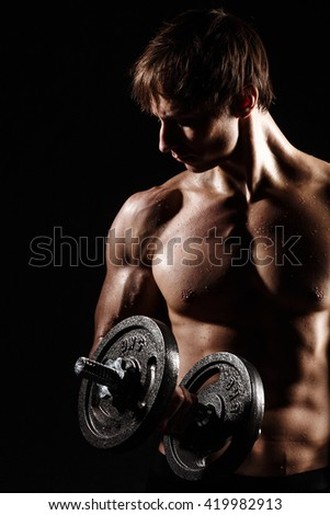 Muscular and fit young bodybuilder fitness male model posing over black background with DUMBBELL. Perfect fitness WET body with DROPS. Ideal for commercial.  - stock photo