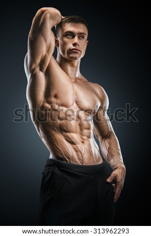 Muscular and fit young fitness male model posing over black background. Strong bodybuilder with six pack, perfect abs, shoulders, biceps, triceps and chest. - stock photo