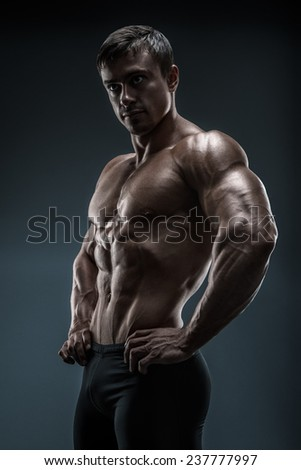 Muscular and fit young man bodybuilder fitness male model posing over black background. Studio shot on black background. - stock photo