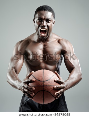 Muscular and serious looking sportsman holding a basketball - stock photo