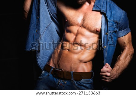 Muscular and sexy body of young sport man in jeans shirt with perfect abs - stock photo
