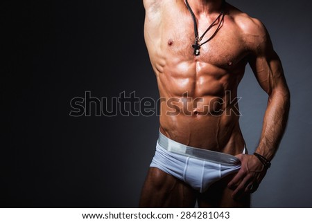 Muscular and sexy torso of young sport man with perfect abs in panties Man striptease. Front view - stock photo