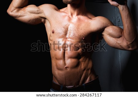 Muscular and sexy torso of young sporty man showing his perfect abs, bicep and body - stock photo