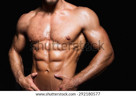 Muscular and sexy torso of young sporty man with perfect abs close up - stock photo