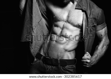 Muscular and sexy young man in jeans shirt with perfect fitness body. Black and white - stock photo