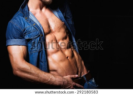 Muscular and sexy young man in jeans shirt with perfect fitness body close up - stock photo
