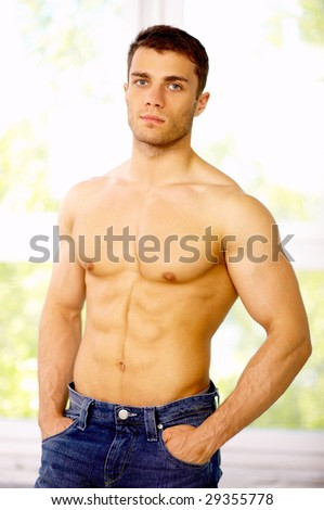 Muscular and tanned male standing near the window - stock photo