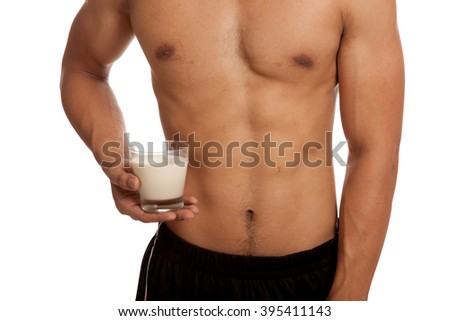 Muscular Asian man show his six pack abs with milk  isolated on white background - stock photo