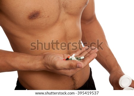 Muscular Asian man show  six pack abs  with some pills  isolated on white background - stock photo
