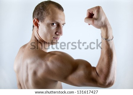 muscular athletic young man showing his huge biceps to the camera - stock photo