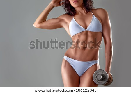muscular athletic young woman in a white bathing suit on a gray background. Fitness. Muscular body. Torso with dumbbells in hand. Abdominal muscles - stock photo