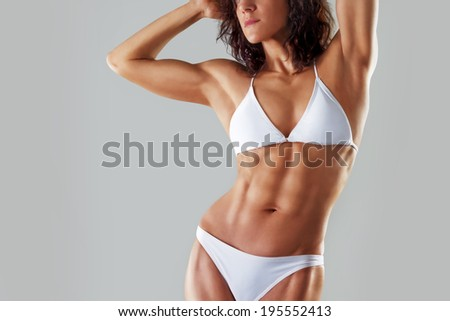 muscular athletic young woman in a white bathing suit on a gray background. Fitness. Muscular body. Torso. Abdominal muscles - stock photo