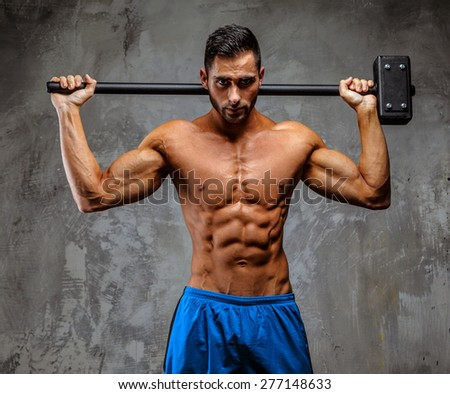 Muscular attractive guy in blue shorts holding hummer on grey background - stock photo