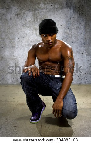 Muscular black male in hip hop style clothing showing abdominal muscles. The man is shirtless and looks physically fit and healthy. - stock photo