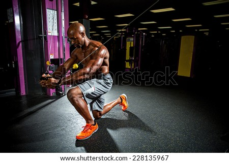 Muscular body builder working out at the gym doing chest fly exercises on the wire cable machine. - stock photo