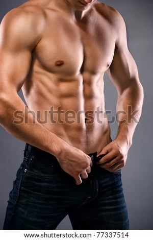 muscular body of young man in jeans. Shot in studio. - stock photo