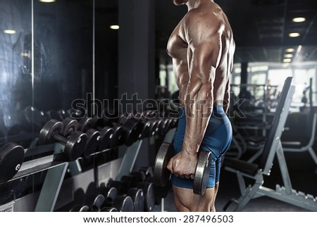 Muscular bodybuilder guy doing exercises with big dumbbell in gym - stock photo