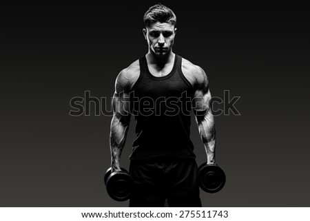 muscular bodybuilder guy  with weights over grey background. Black and white - stock photo