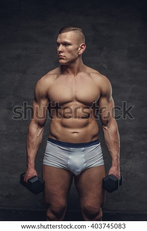 Muscular bodybuilder in a white panties holds a pair of dumbbells. - stock photo