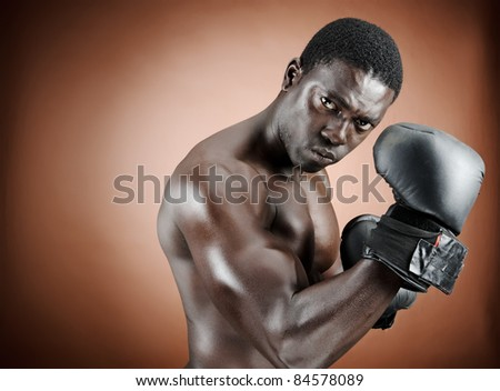 Muscular boxer flexing his biceps during his workout - stock photo