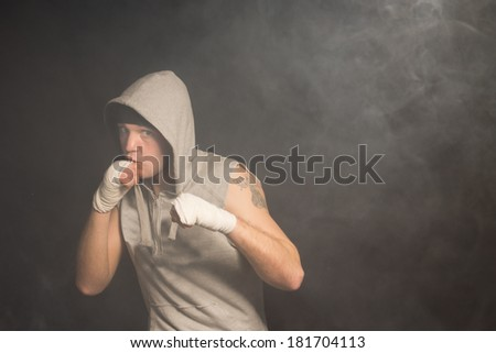 Muscular boxer ready for a fight standing with his fists raised looking out intently from under his hooded top as he watches his opponent carefully against a dark background with copyspace - stock photo